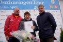 Uwe Jahn, Präsident des Thüringer Radsport-Verbandes, und Tour-Gesamtleiter Wolfgang Reichert ehren Ilona Wenzel für ihr ehrenamtliches Engagement mit der TRV-Ehrennadel